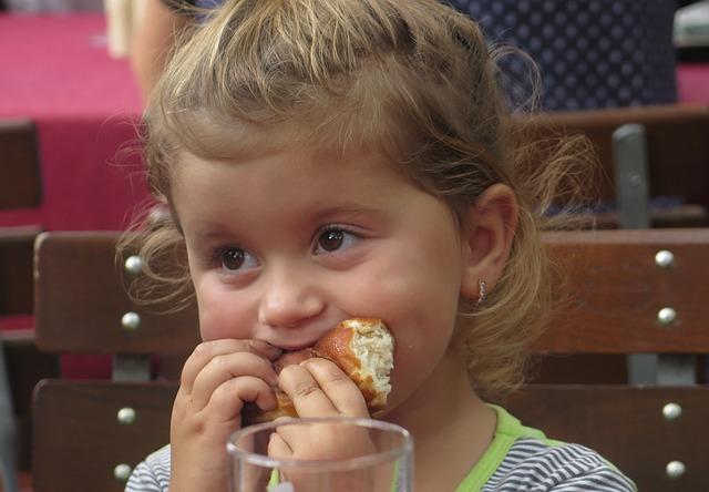 dziewczynka je pączka