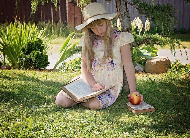 dziewczynka czyta książkę na świeżym powietrzu